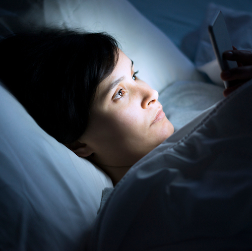 Woman using her phone under blanket in bed at night, get fit, blue light, technology before bedtime, answering work emails