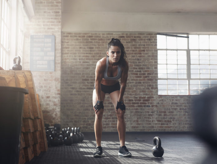 fitness, Full length shot of confident young woman at gym gym. Muscular sportswoman standing with her hands on knees looking focused about her fitness workout.