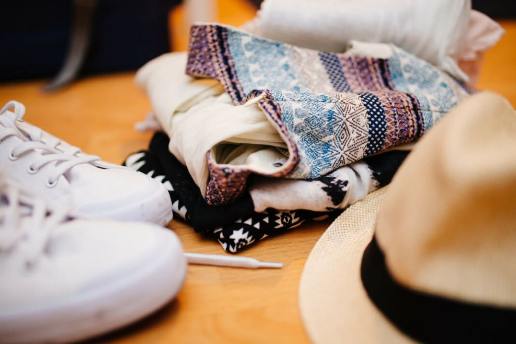 Sneakers, a hat and a pile of clothing ready to be packed into a suitcase.