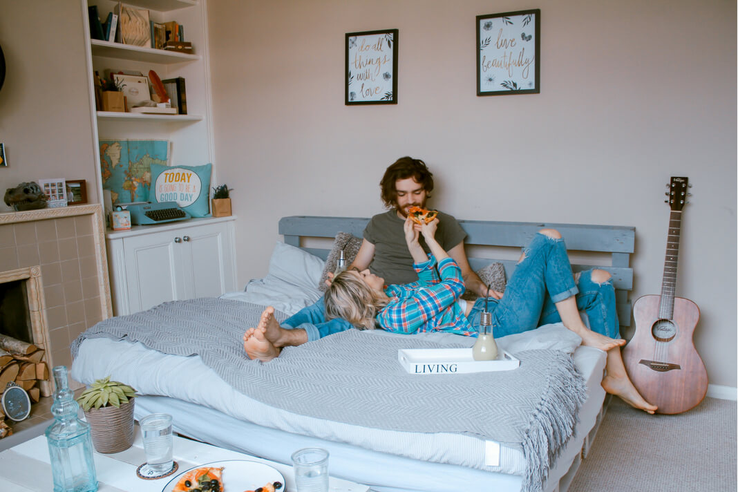 Couple sitting in bed with one partner feeding the other a slice of pizza.