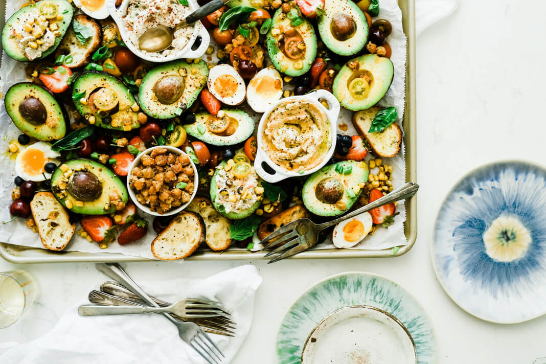 A platter with a healthy mixture of foods including bread and dairy.