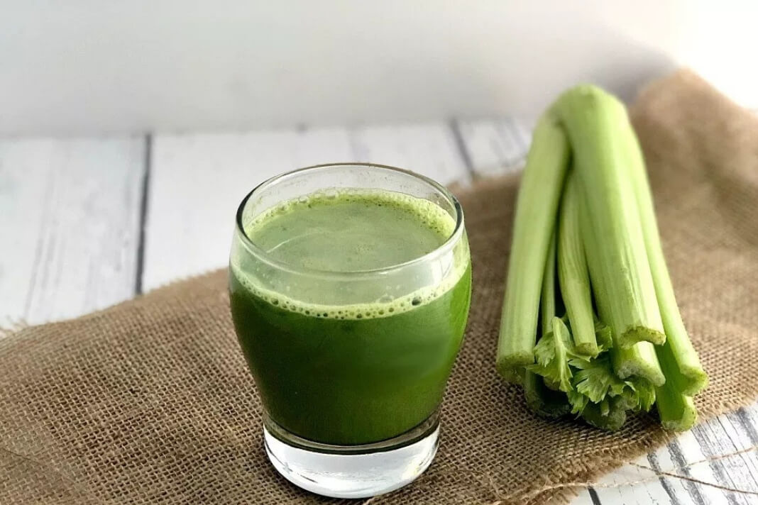 A glass of celery juice with celery stalks placed beside it.