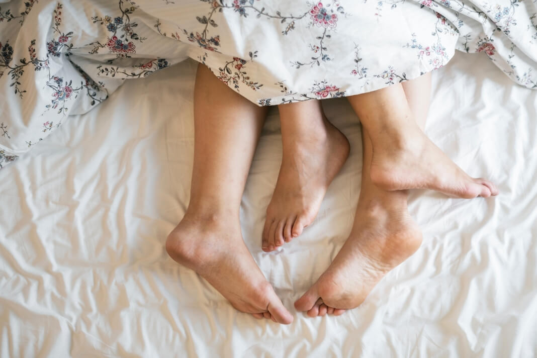 Picture of two people's feet intertwined at the end of a bed.
