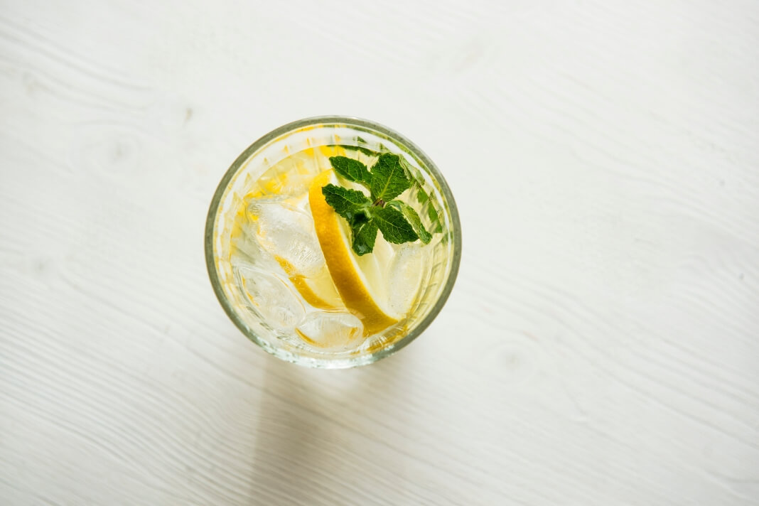 Glass of water with ice, lemon and mint.