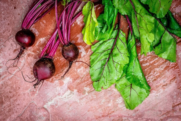 Image of beets on a pink marble background.