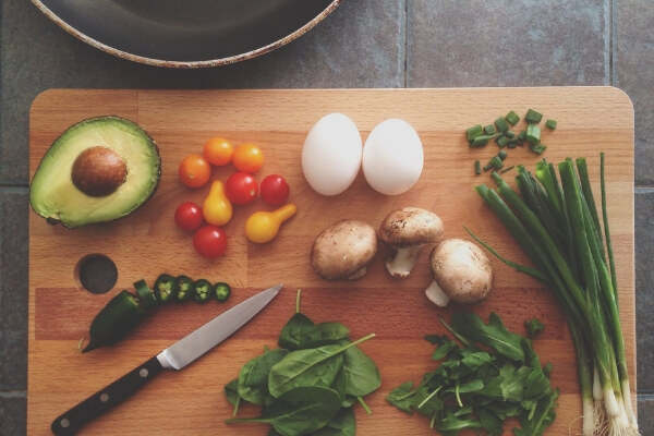Image of vegetables, eggs and avocado on a chopping board.