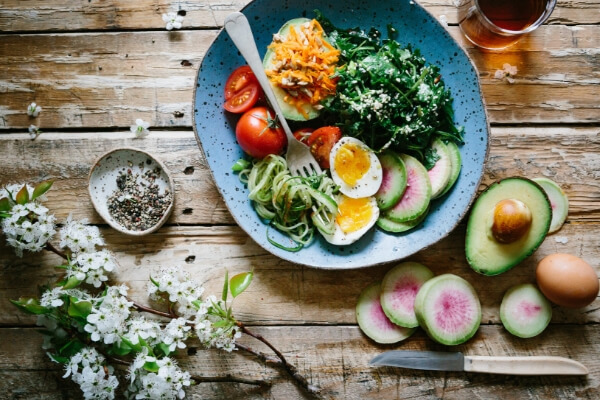 Image of a healthy, colourful meal with flowers placed next to it.