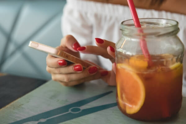 Woman with painted nails typing on her phone next to a jar of juice.