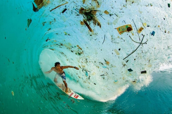 Surfer in a barrel wave surrounded by floating plastic rubbish.