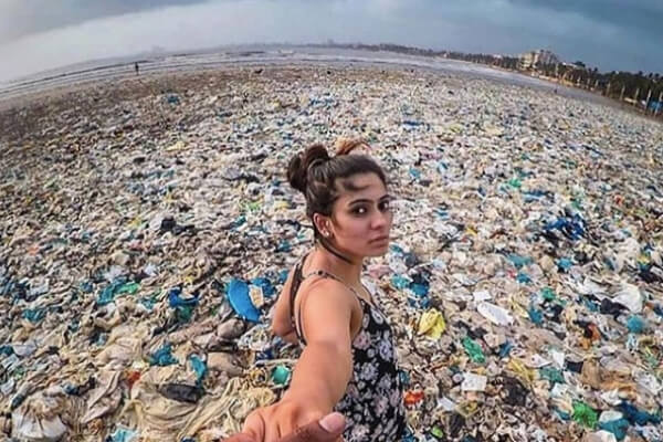 Woman against the backdrop of a plastic-infested beach.