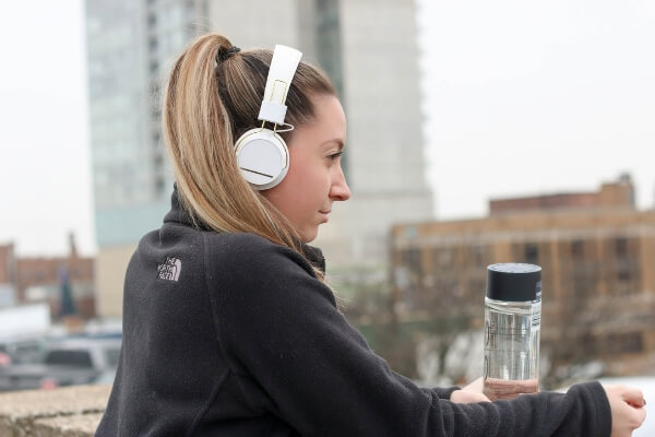 Woman with headphones on standing with a glass water bottle.