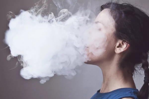Woman in a cloud of vape from vaping.