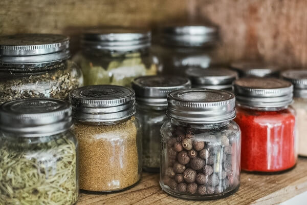 Image of herbs and adaptogens in glass jars on a wooden shelf.