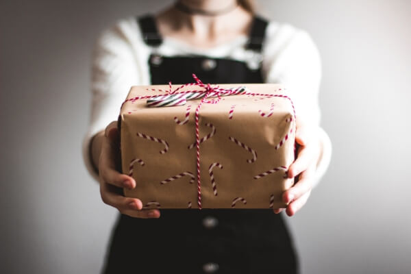 Woman holding out wrapped gift eco-friendly