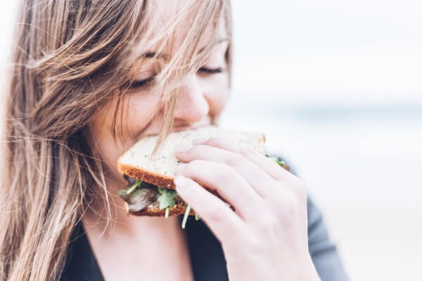 Image of a woman eating a healthy sandwich on the go.