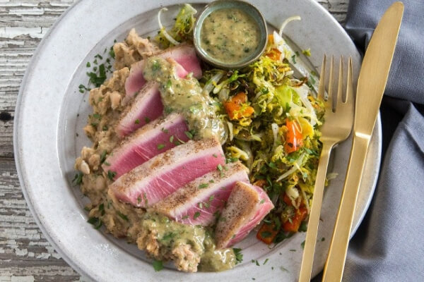 Image of a seared tuna steak with accompanying salads.