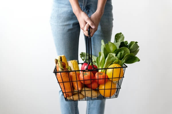 Image of a woman holding a basket full of groceries.