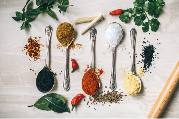 Image of herbs and spices on teaspoons surrounded by garnishes.