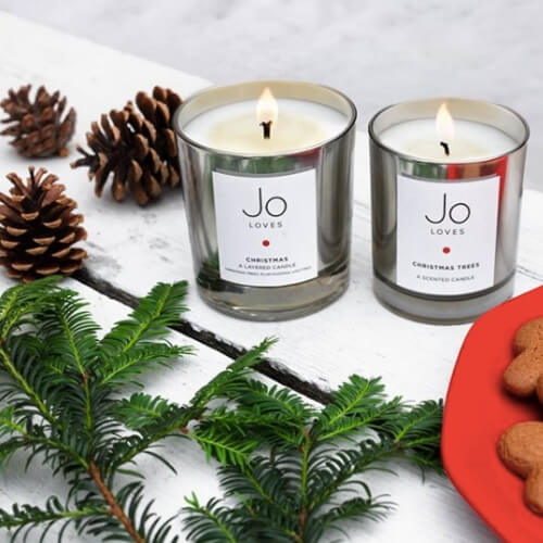Image of two Christmas candle surrounded by pine cones and mistletoe.