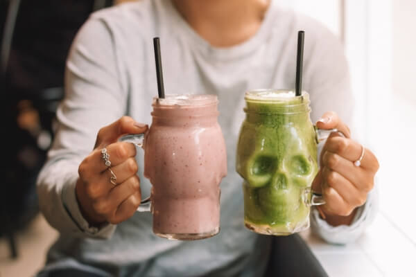 Image of a woman holding two different-coloured smoothies in fun glasses with straws.