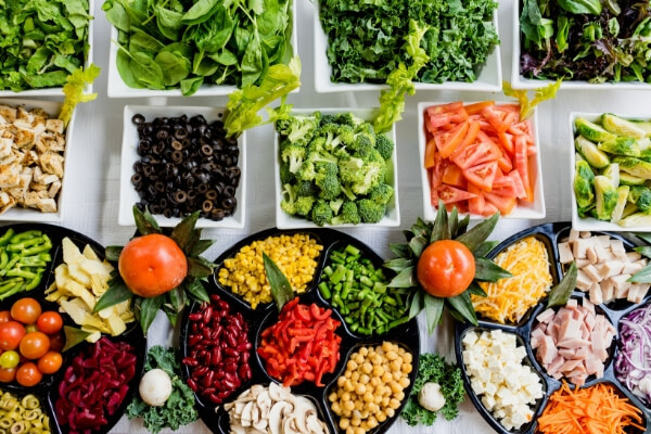 Image of a salad bar with lots of fresh vegetables.