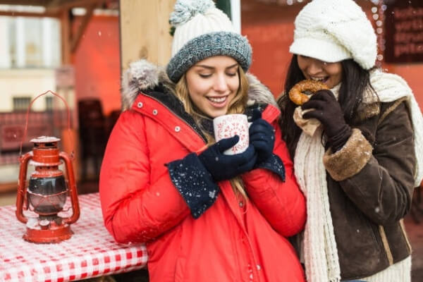 Two women at a Christmas market laughing.