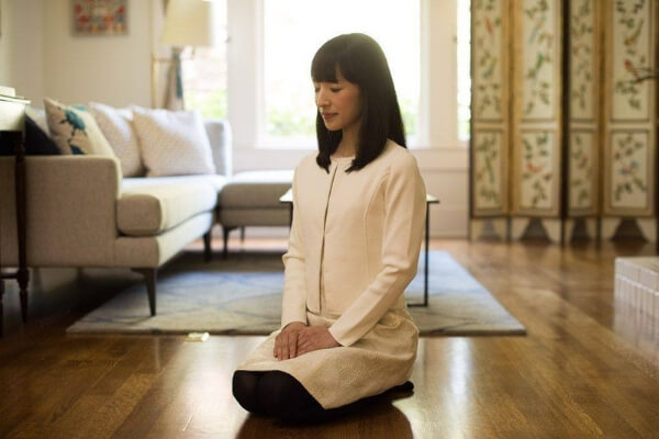 Marie Kondo meditating in a home.