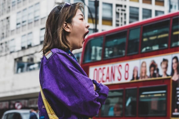 Woman yawning in front of a bus