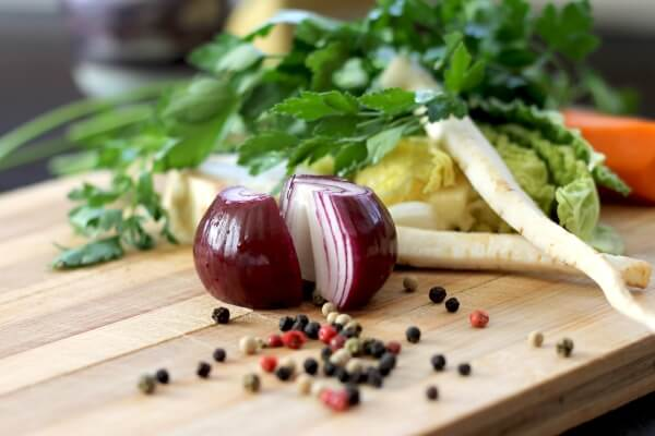 Image of red onion and other vegetables in background on a chopping board.
