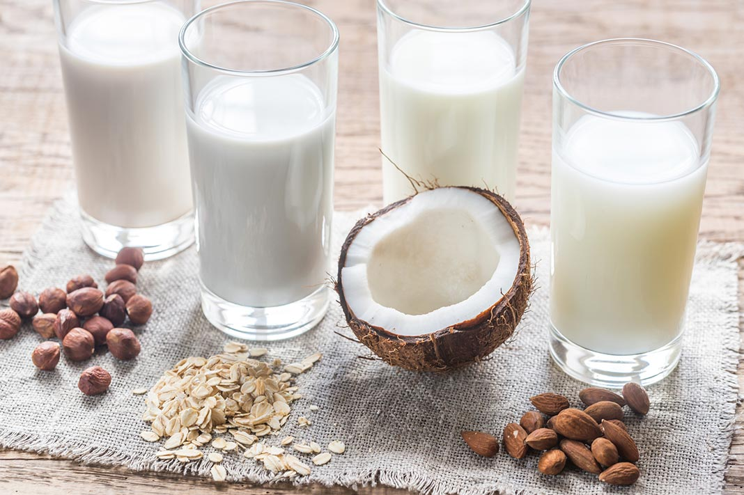 best non-dairy alternative milk, glasses of milk and a coconut