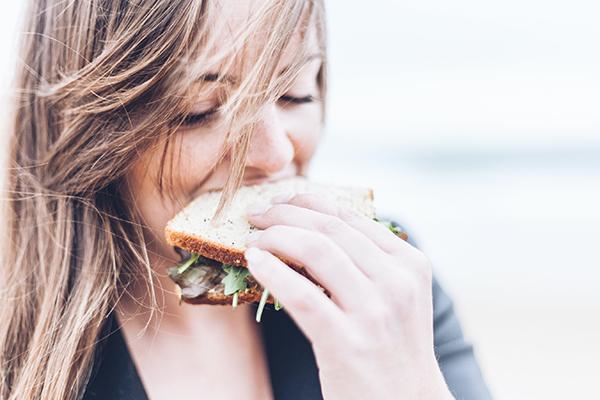 femme mangeant un sandwich, comment faire le jeûne intermittent